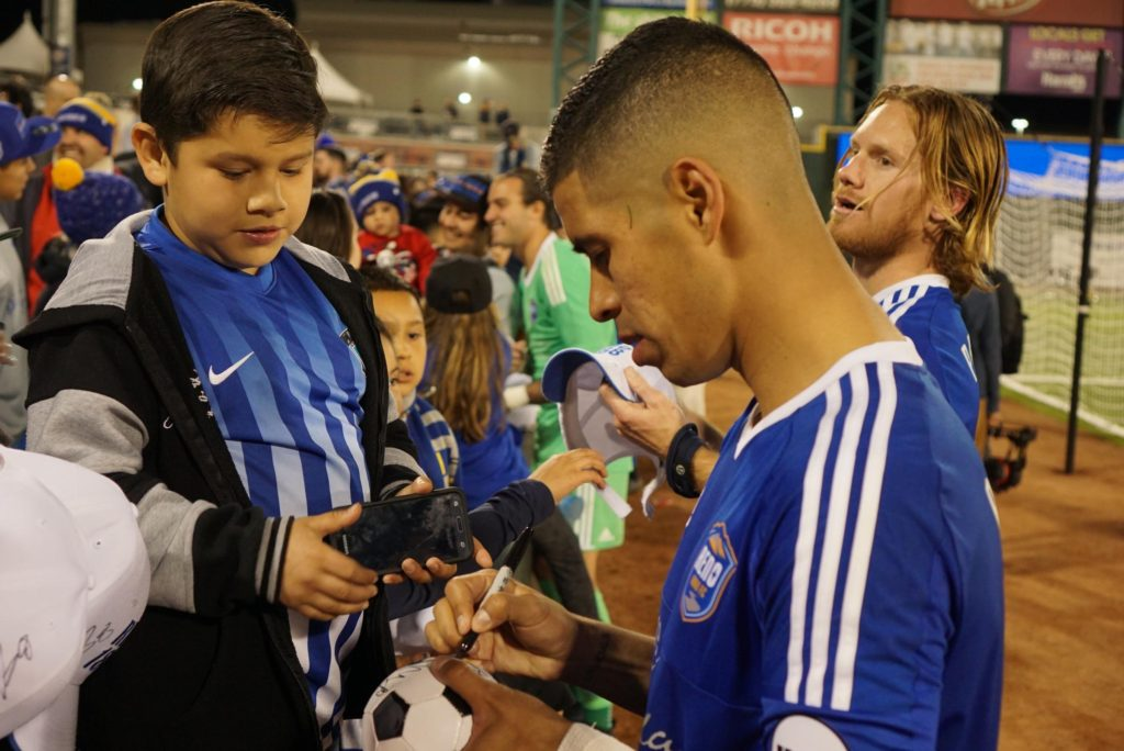 Junior Burgos signs autographs at the end of the game. Fans are willing to get anything signed from Burgos, including T-shirts and mini soccer balls.