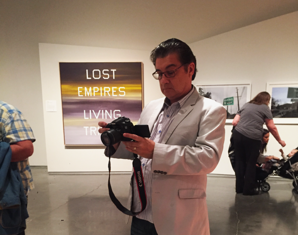 Guillermo Bert proudly takes pictures of his pieces displayed in the exhibition, standing back and reviewing them carefully.
