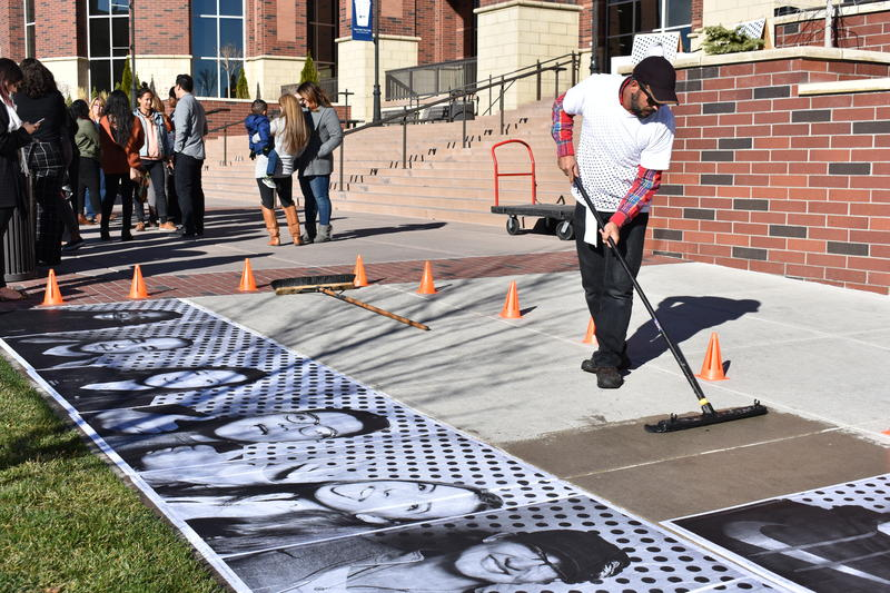 An artist with the Inside Out Dreamers Project pastes photos of UNR students on the sidewalk who had their photos taken to show solidarity with Dreamers. CREDIT: Natalie Van Hoozer