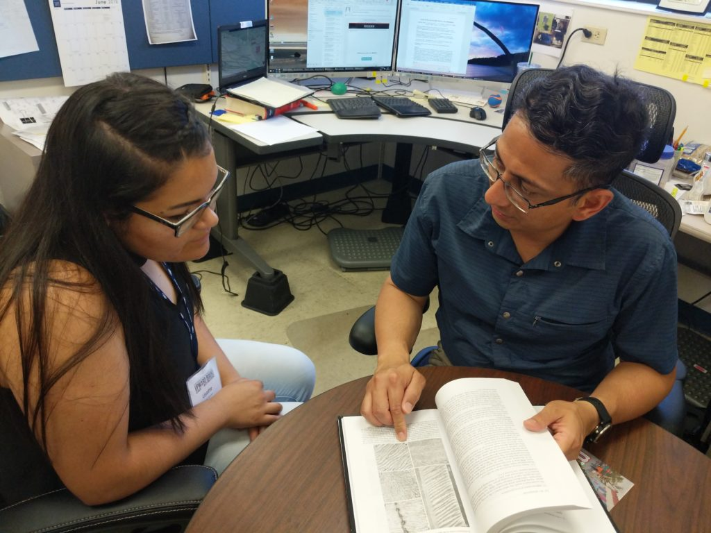 Dr. Pathak working with a fellow student.