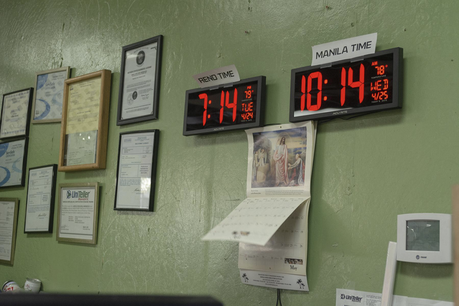 Two digital clocks hanging on a wall, depiciting the time for Reno and Manila.