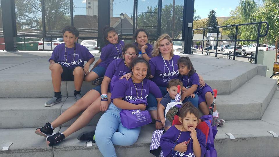 Family sits in purple shirts for youth suicide prevention