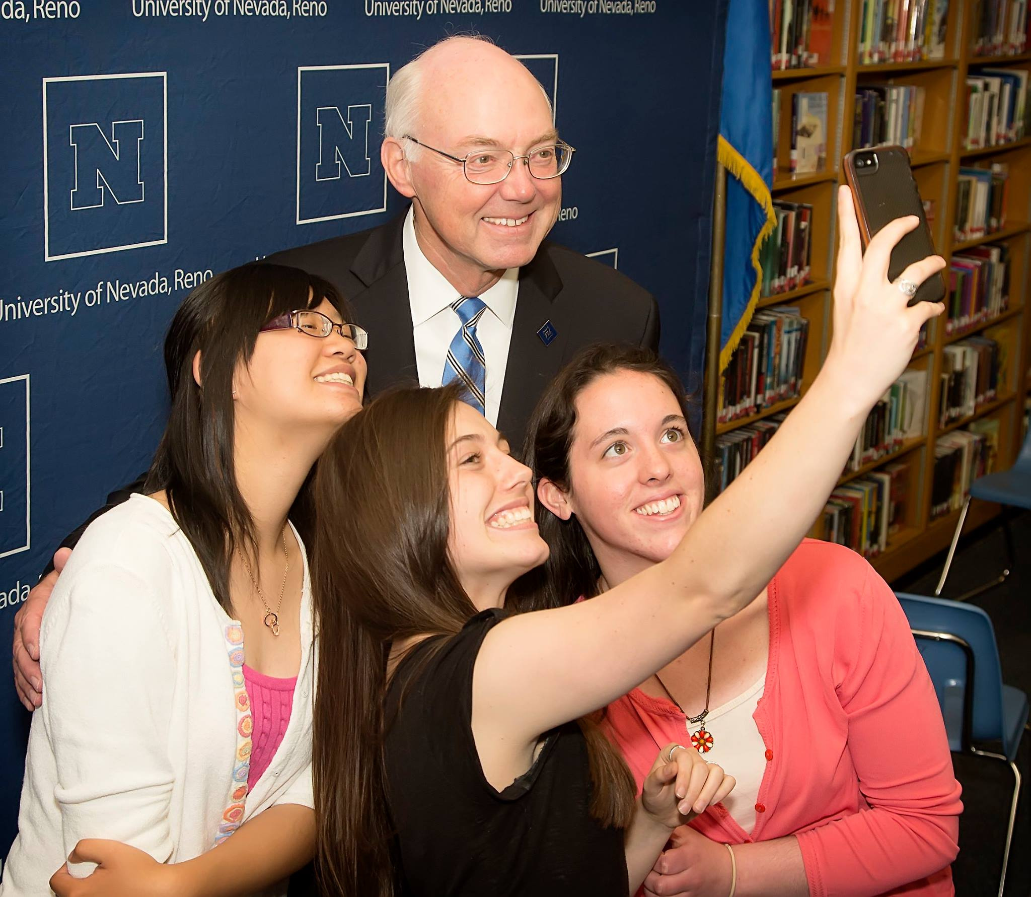 UNR's President, Marc Johnson, taking a selfie three UNR students.