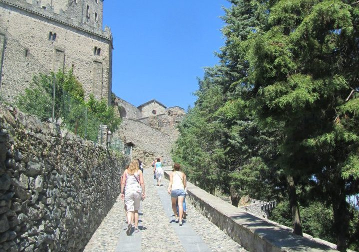 Women walking up stone path leading to old buildings in Torino, Italy.