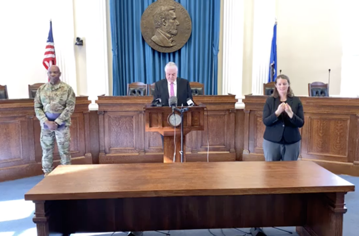 Gov. Sisolak at a podium making an announcement, with a sign language interpreter and National Guard officer flanking him at a distance.