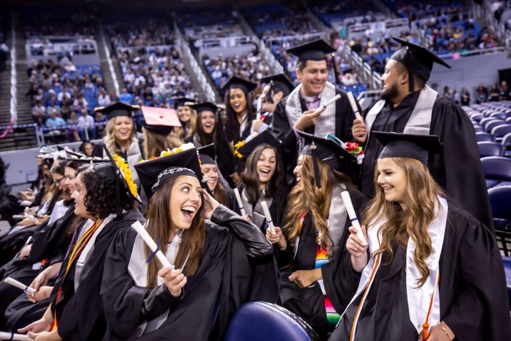 Recent graduates from the University of Nevada-Reno, smiling at one another after receiving diplomas.