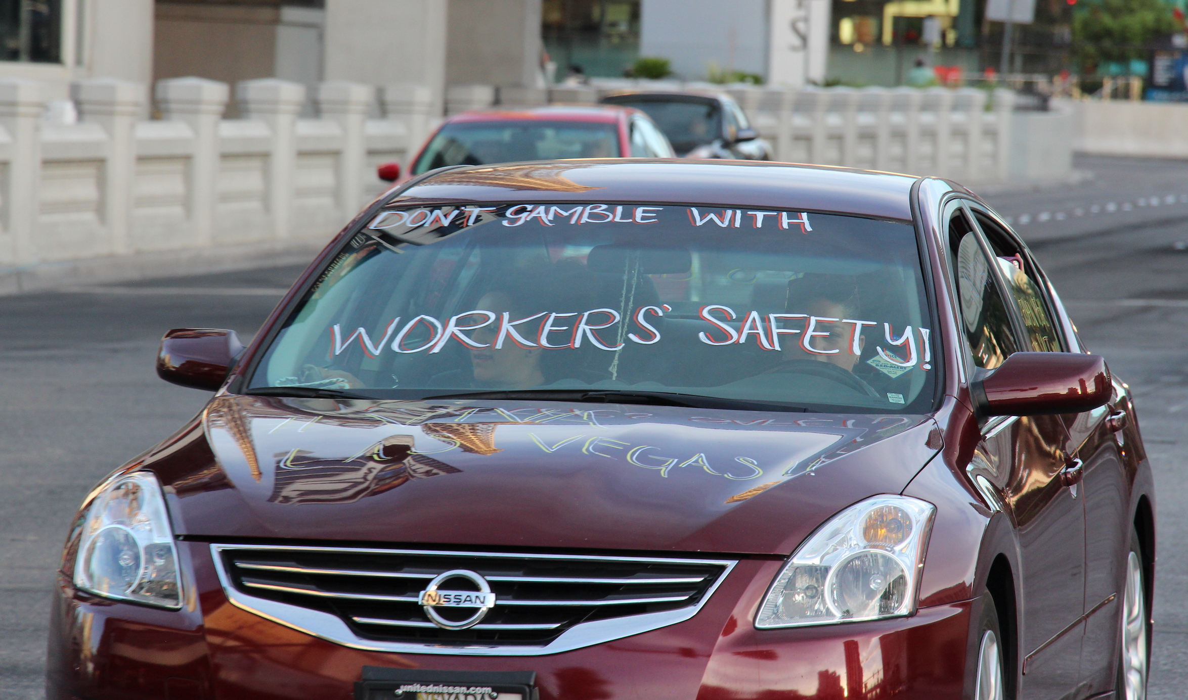 """Casino workers in vehicle with words on windshield that read, """"Don't gamble with workers' safety."""""""