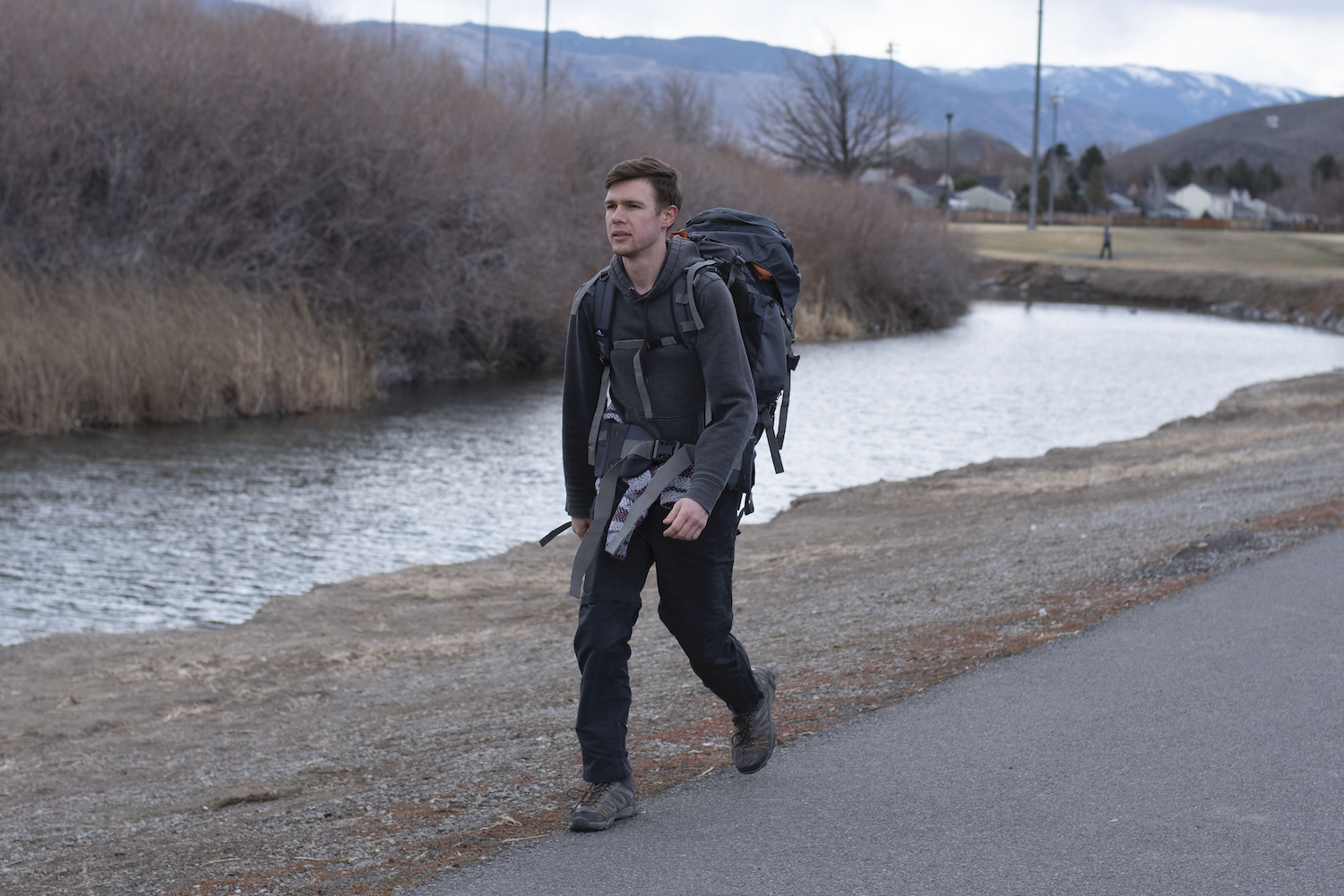 Young man with backpack walking on the side of the road.