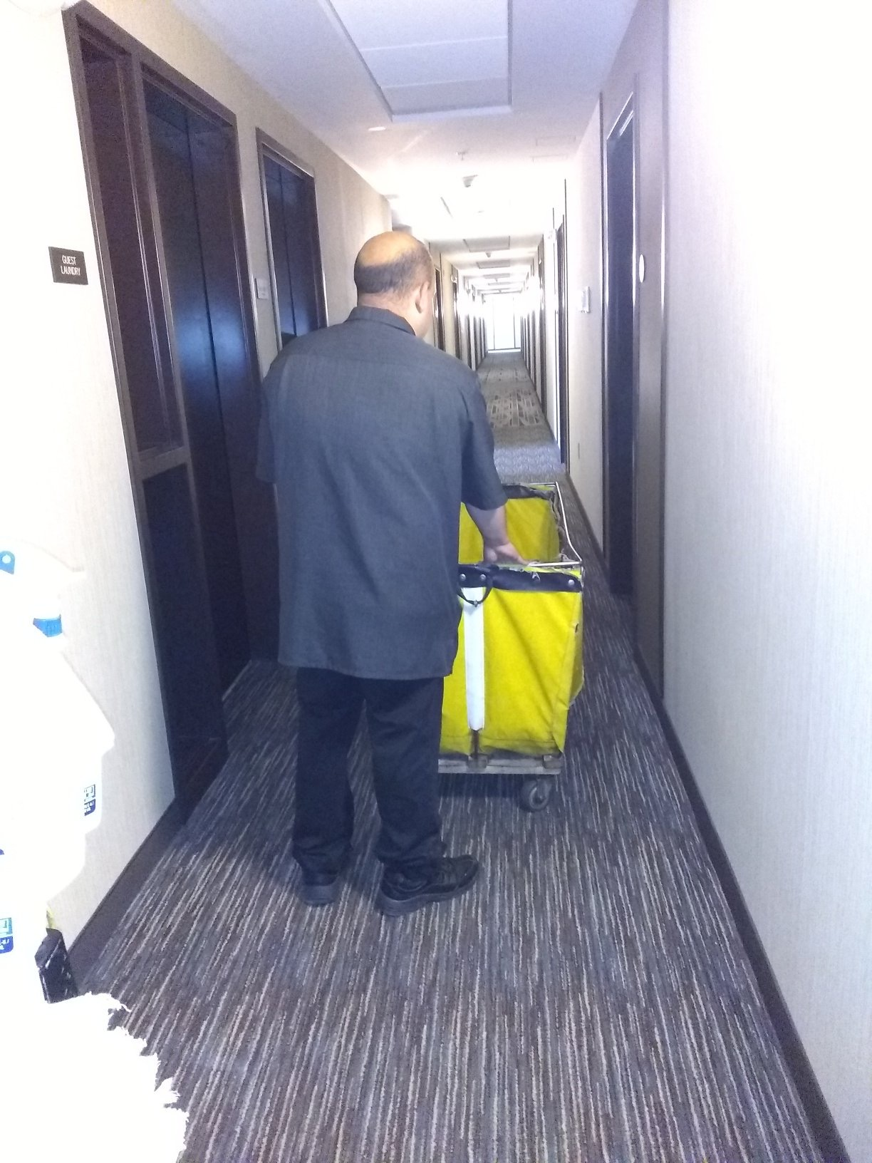 View of a man's back as he pushes janitor cart
