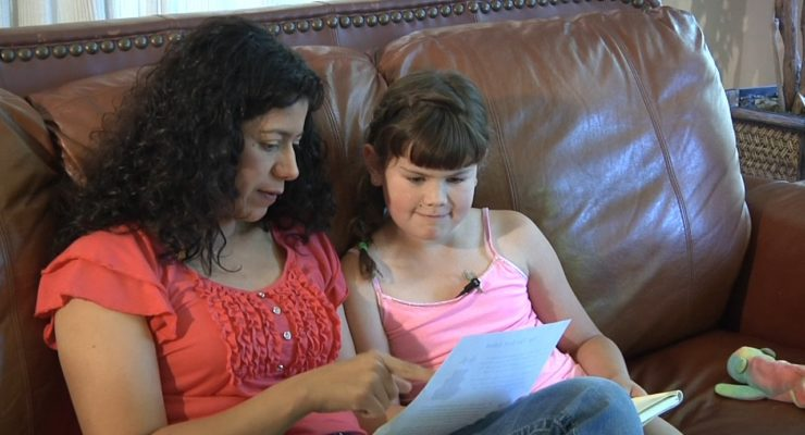 Mom reviews lesson with daughter on couch at home.
