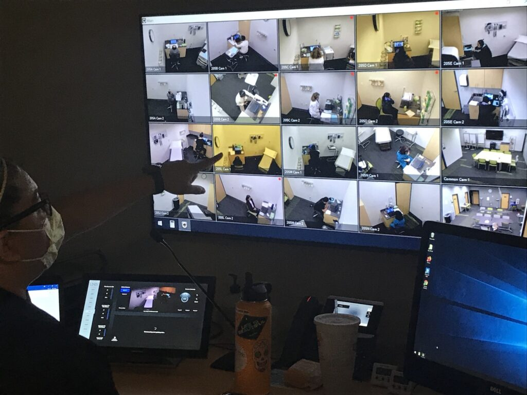 Monitor showing images of people in different rooms