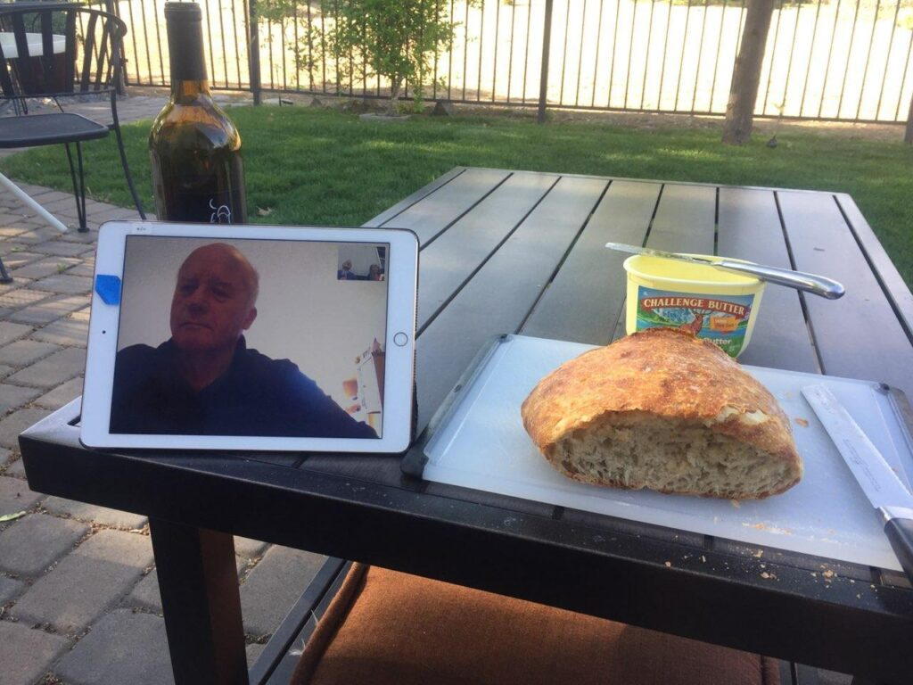 IPad on table with video image of Jim Ashurst. On table is a bottle of wine, sourdough bread and margarine.