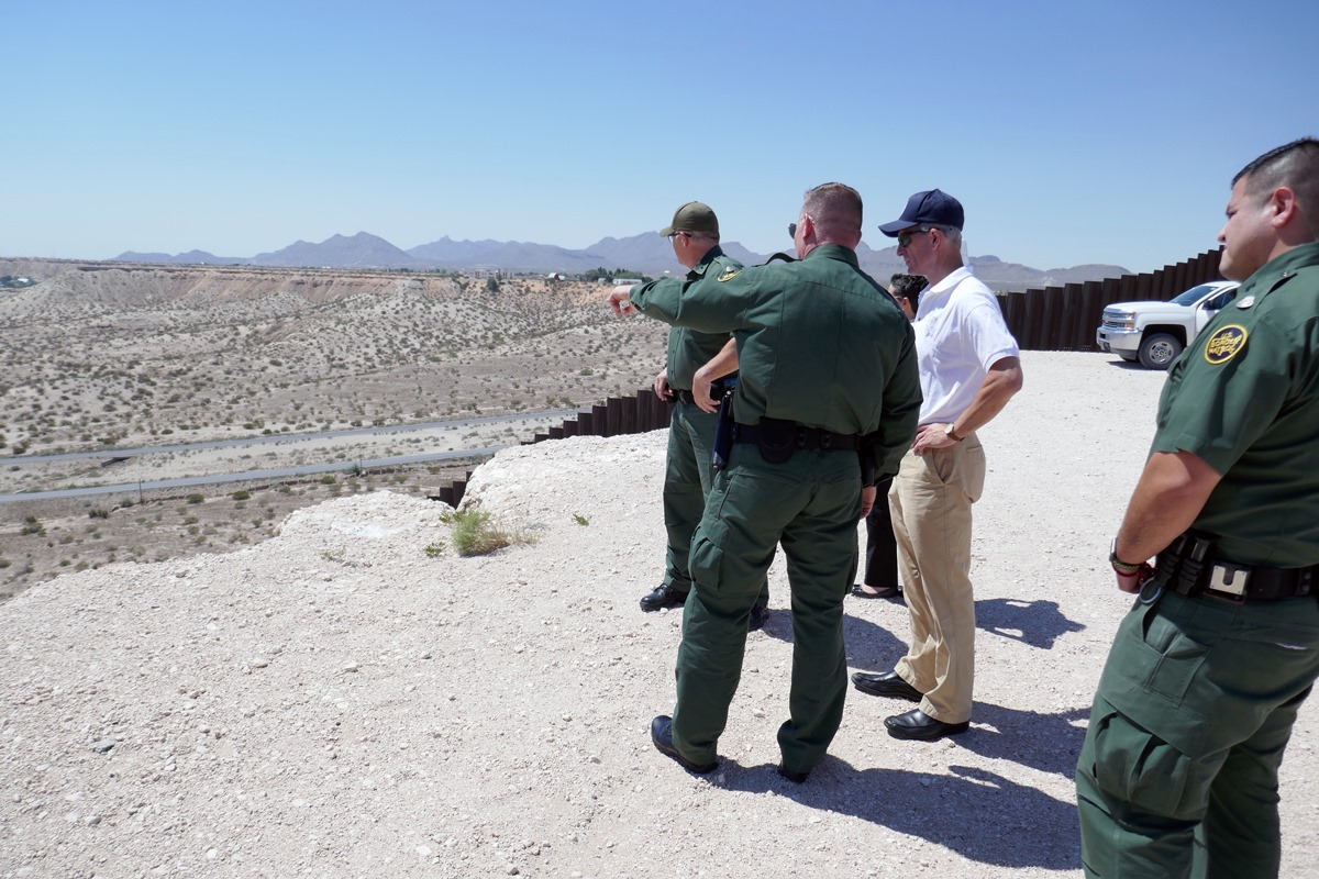 Border Patrol agents alongside the border wall.