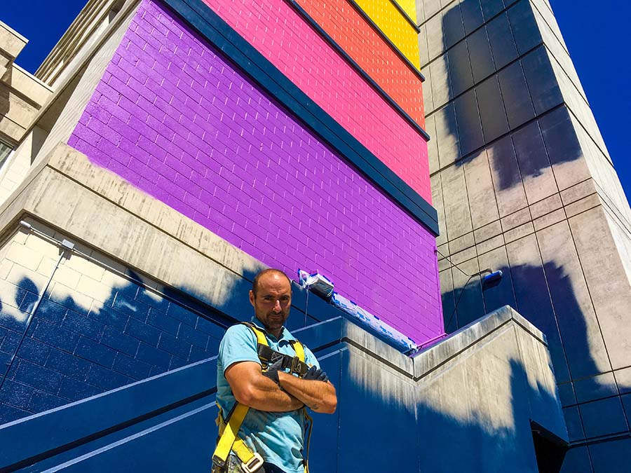 Muralist Rafael Blanco poses for a photo in front of his unfinished mural.