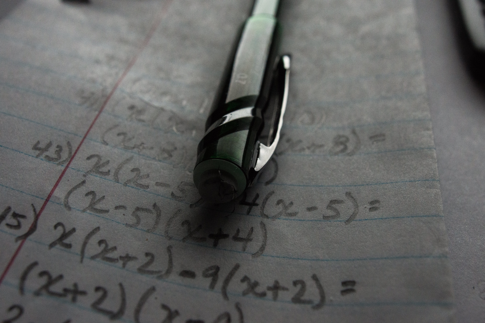 Math formulas written on lined paper with a pen resting on top. Unlike the math homework pictured above, Piceno says that due to COVID-19, he converted all his coursework to digital assignment to avoid passing papers back and forth with students.
