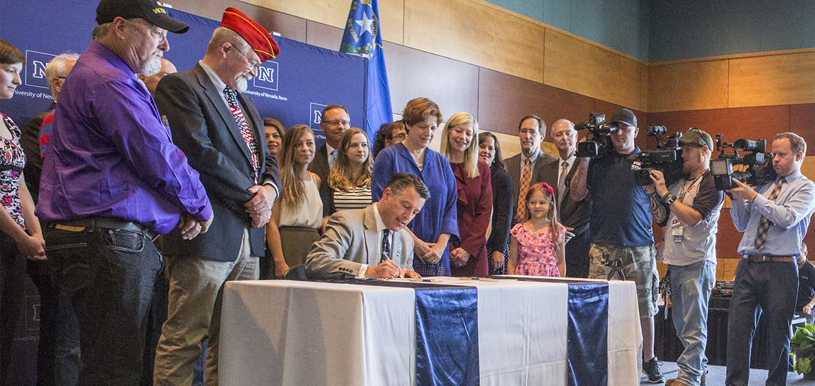 Former Nevada Governor Brian Sandoval seen here at a Senate Bill signing at the university surrounded by people.