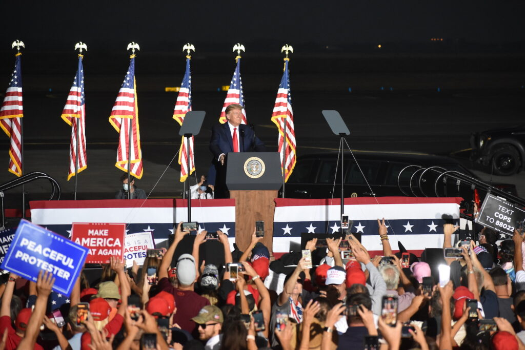 President Donald Trump stands behind a podium in front of four U.S. flags on a platform in front of attendees at the Minden-Tahoe Airport in Nevada.