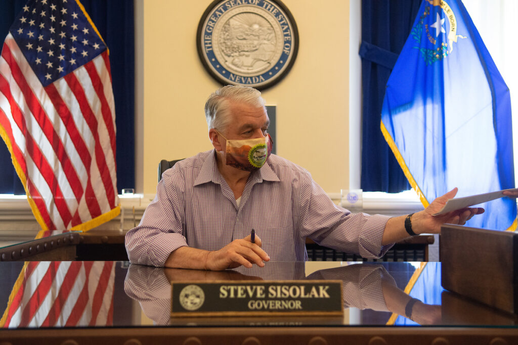 Nevada Governor Steve Sisolak sitting at his desk in the Capital building.