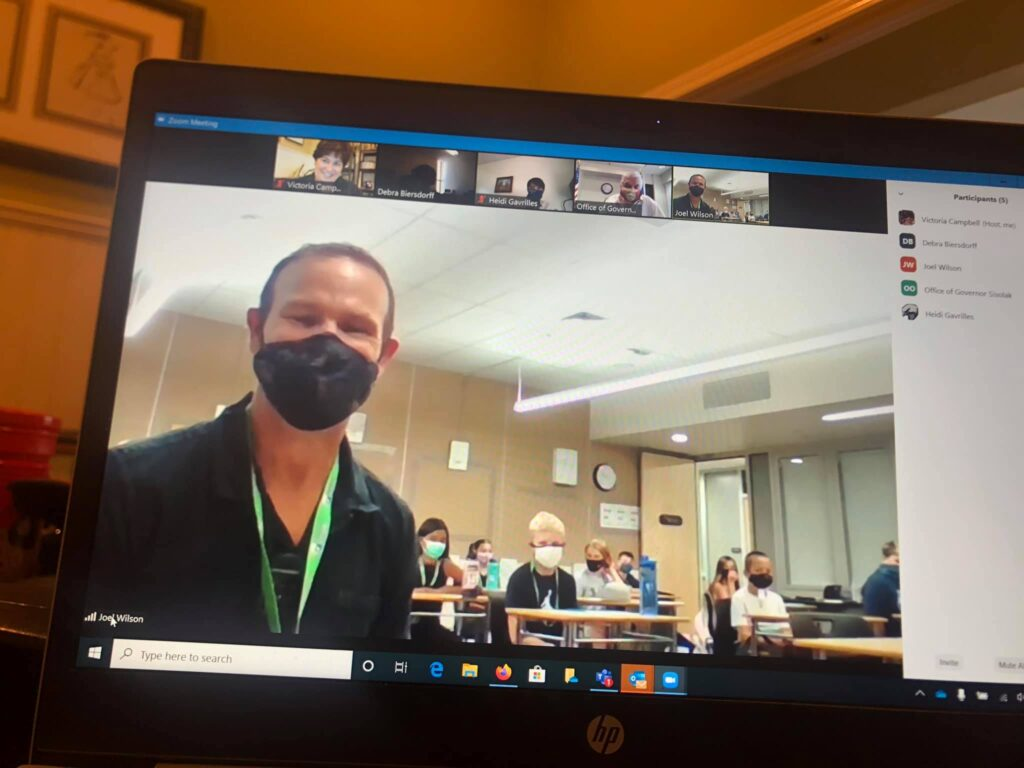 Teacher wearing a mask can be seen via Zoom on computer screen. Behind him is a class of students also wearing masks.