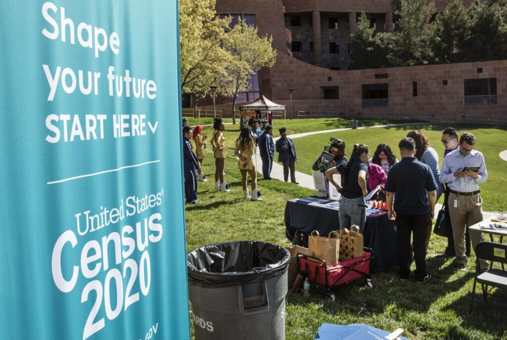 """Sign that reads """"Shape our future, start here"""" with Census 2020 logo beneath. The sign is nearby people completing the census form."""