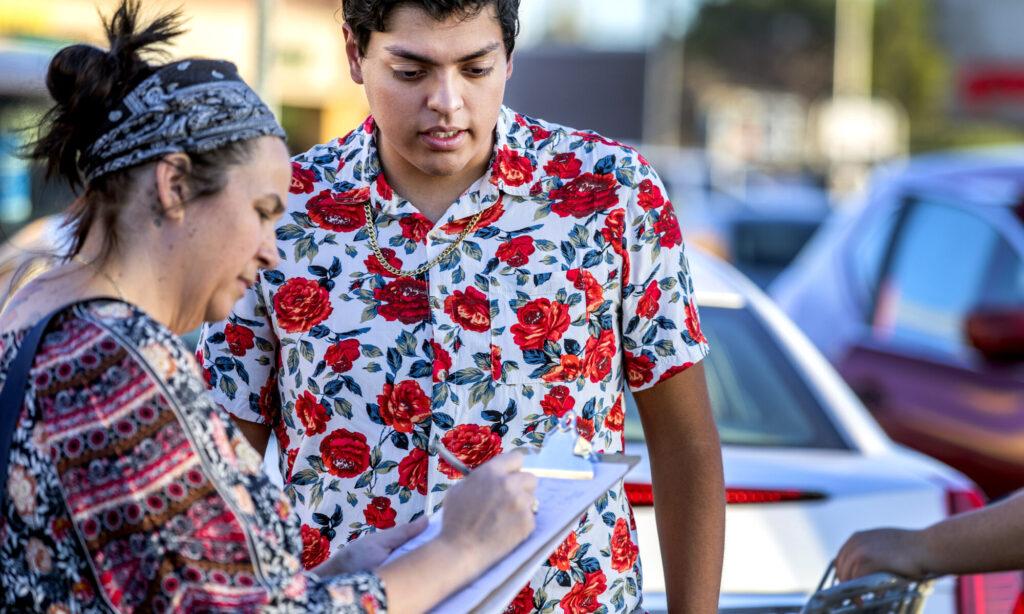 Una mujer rellena un formulario mientras un joven la observa