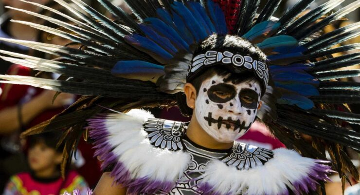 Young boy with skeleton face paint and dressed in a native costume