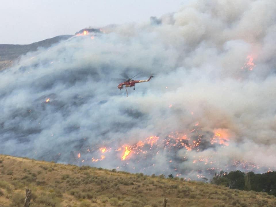 A helicopter dumps water or another fire retardant over wild land.