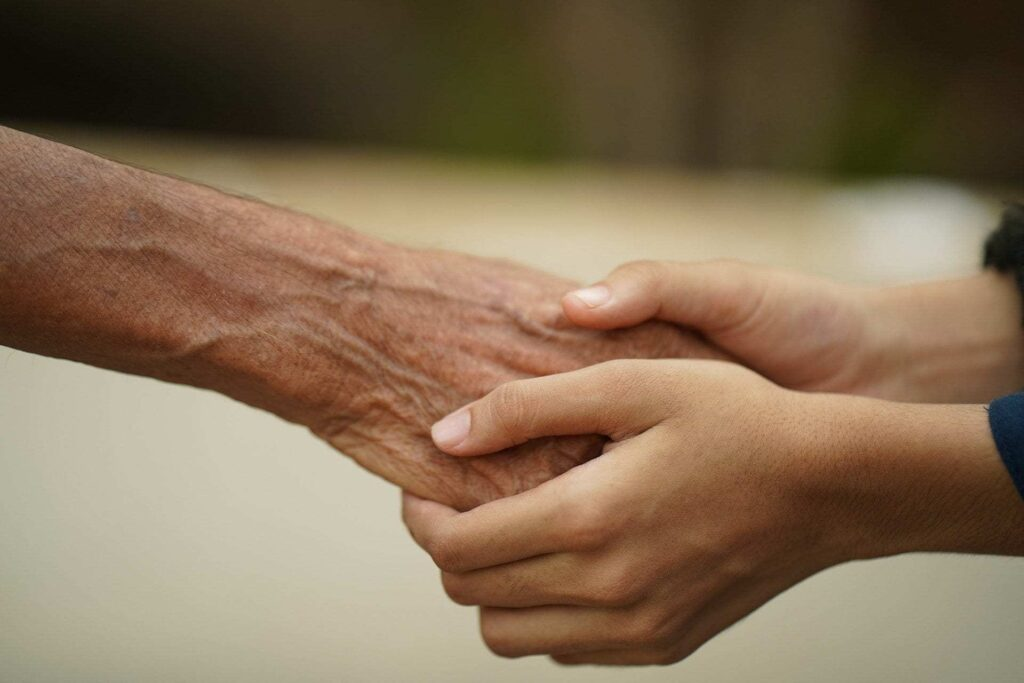 A young person's hands take those of an older person