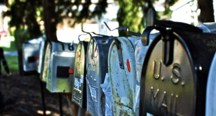 A row of street mailboxes beneath some trees