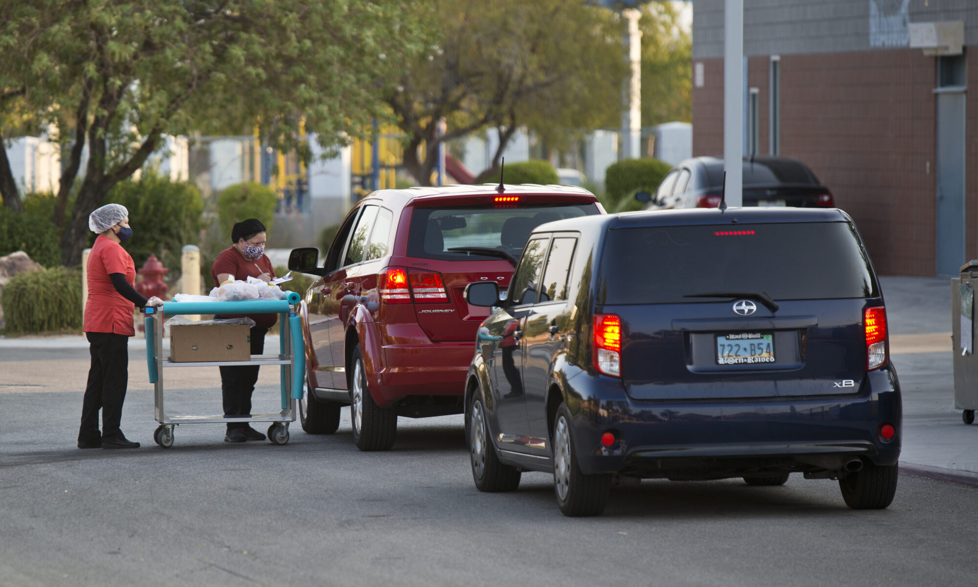 School workers distribute food to a person through the window of their car.