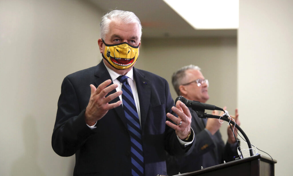 Nevada Governor Steve Sisolak responds to a question during a news conference. The face mask is themed after the Vegas Golden Knight's mascot Chance the Golden Gila Monster.