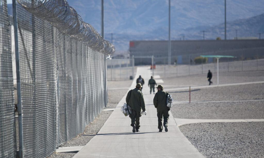 Guards walk inside High Desert State Prison