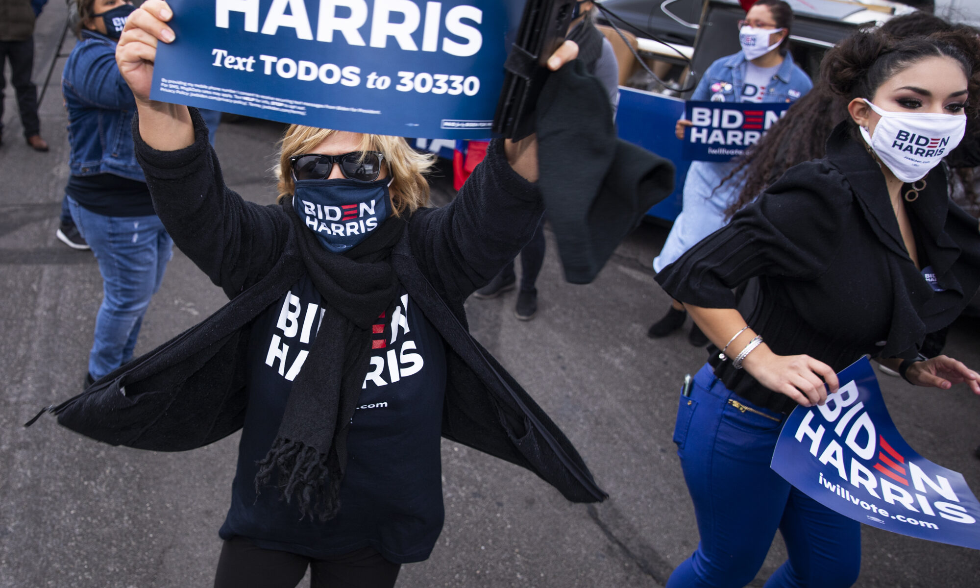 people with posters por Biden and Harris celebrate