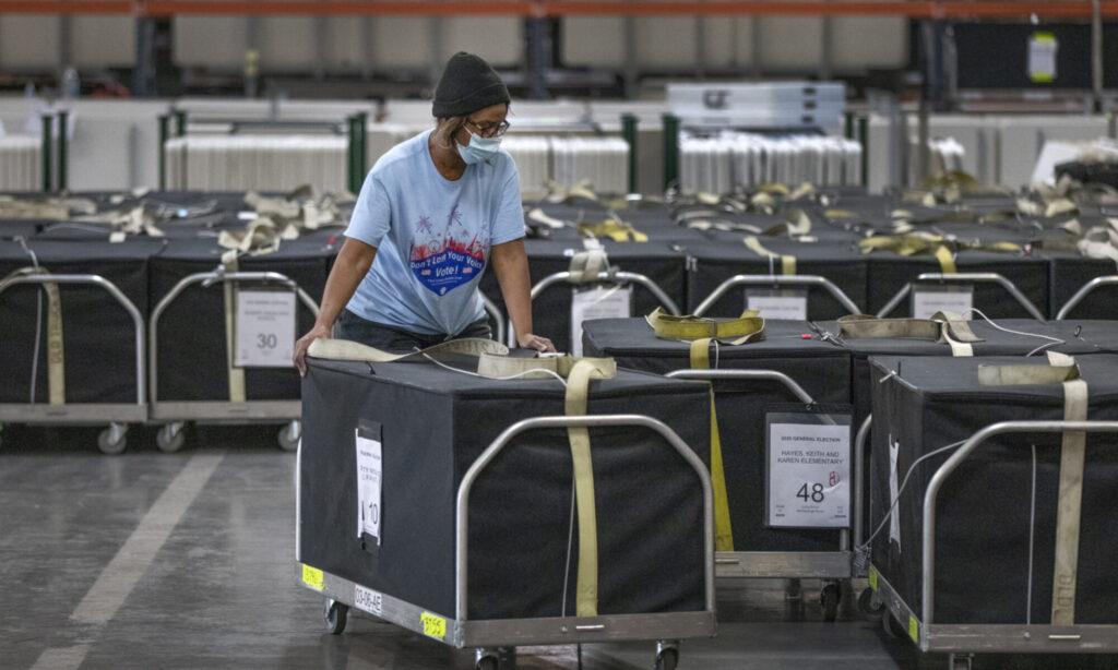 registrar of voter staffer wheels cart with ballots