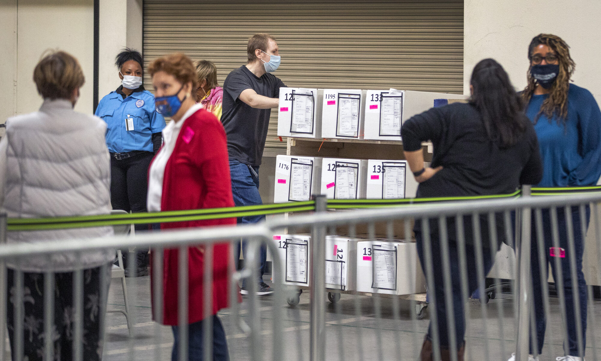 A masked man pushes a cart full of ballots pass observers