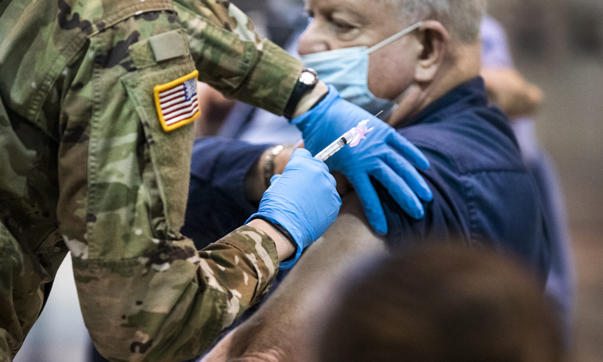 A National Guard member injects elderly man with COVID-19 vaccine