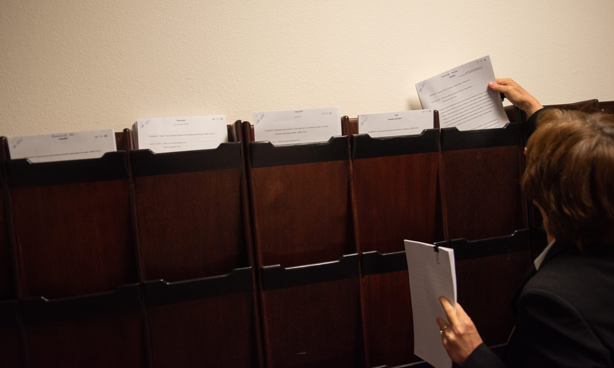 A man placing copies in cubbies