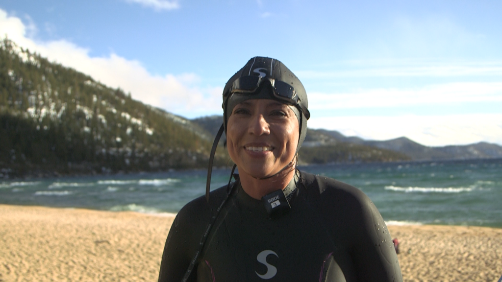 A woman in a wetsuit poses at a lake