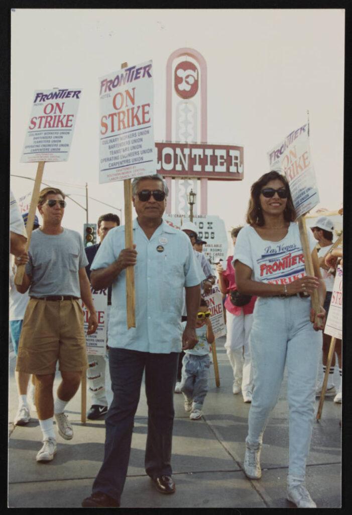 César Chávez with picket sign walks with Geoconda Argüello-Kilne
