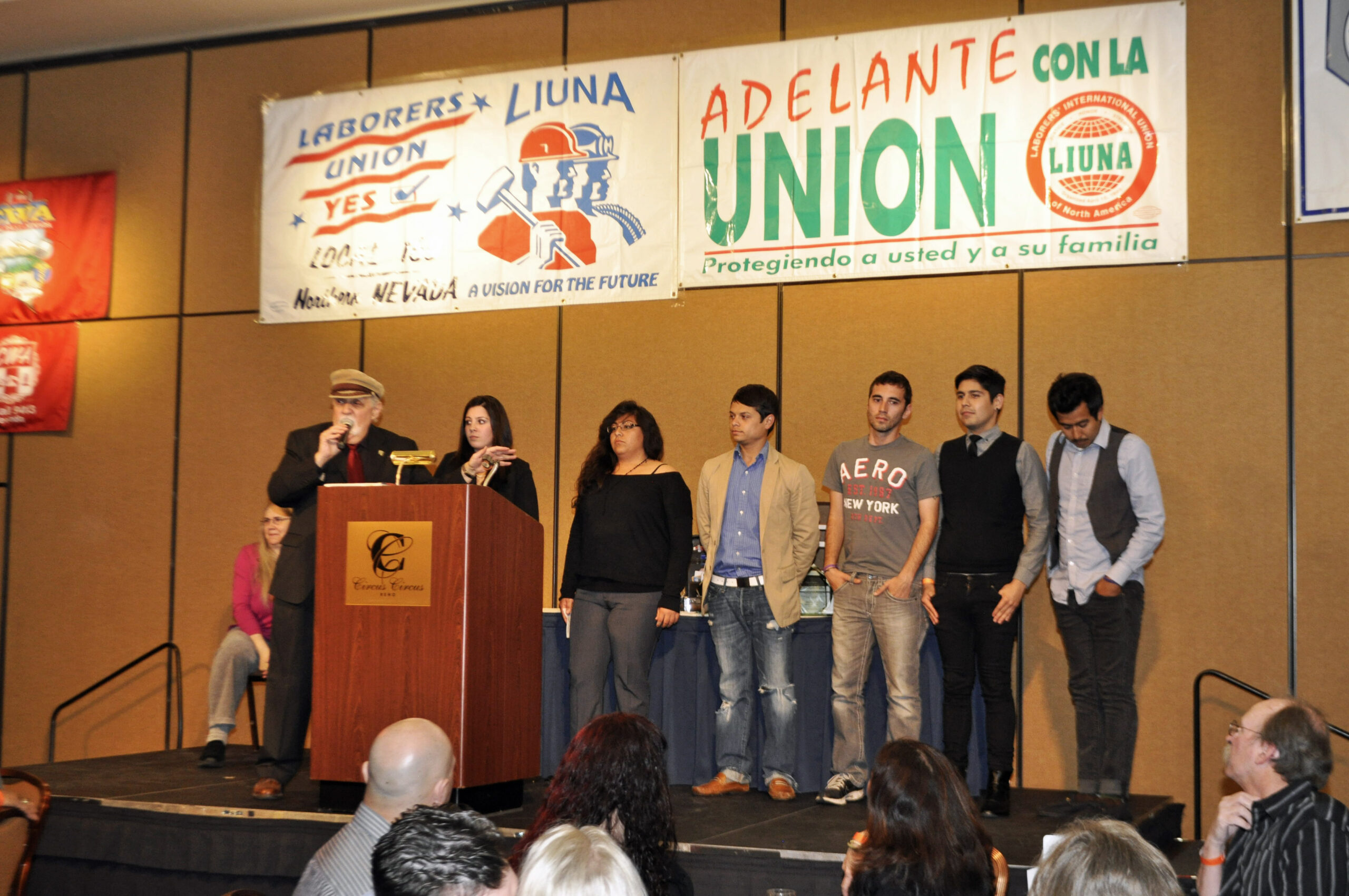 Students on stage with union banners behind them