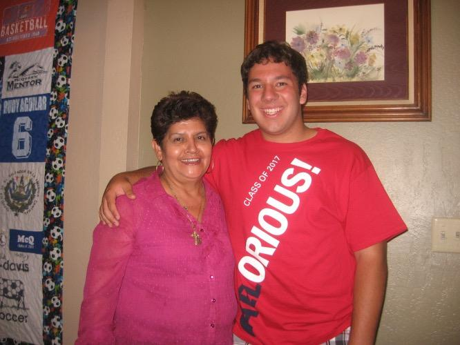 A woman in a pink blouse and her nephew in a red shirt smiling