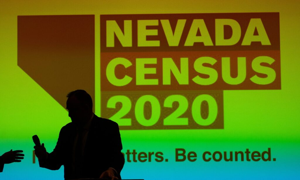 A man posing in front of a screen that reads Nevada Census 2020