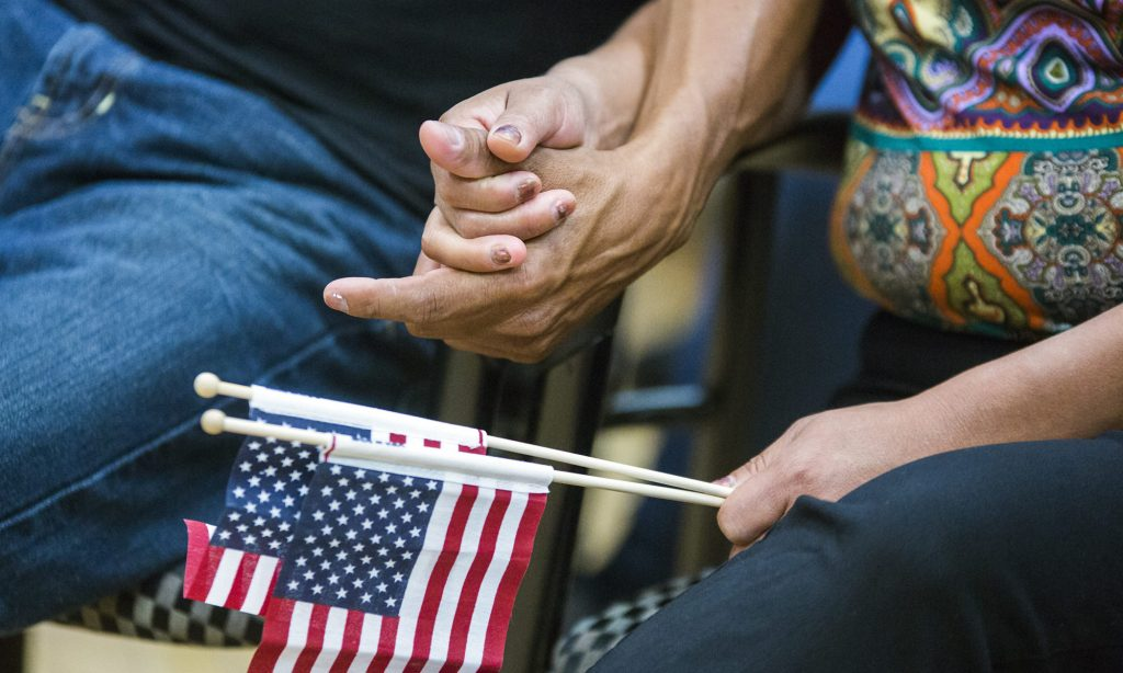 Two persons holding hands, one with the U.S. flag