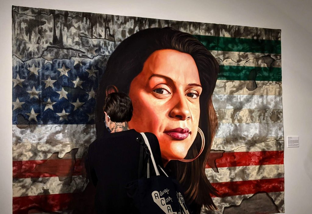 A woman looks closely at a painting of a woman's face in front of U.S. and Mexican flags.