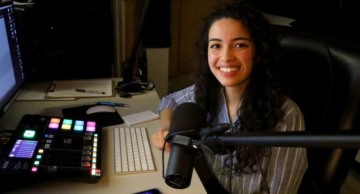 woman smiling seated in radio booth