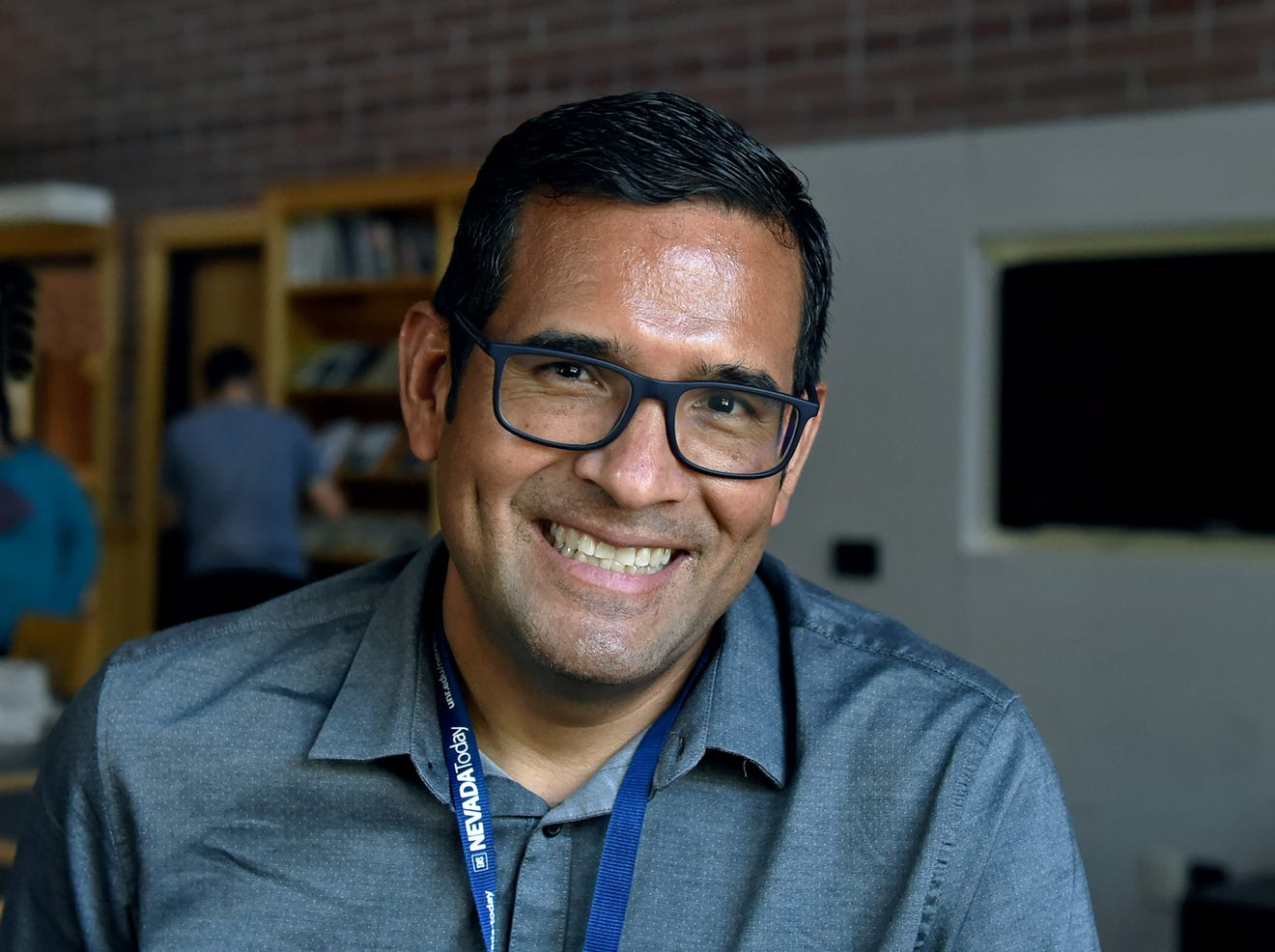A man with eyeglasses poses in front of the camera